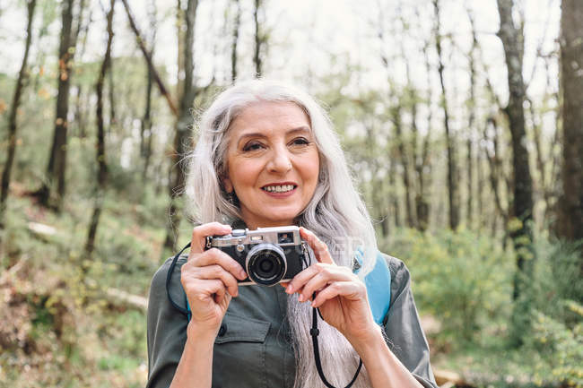 Woman with grey hair photographing in forest — Stock Photo