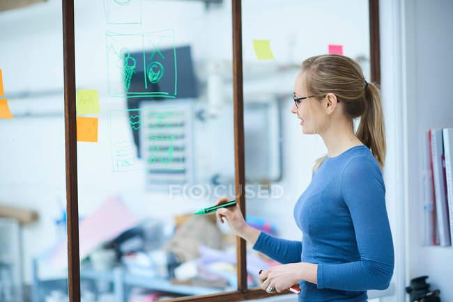 Diseñador mujer en ventana - foto de stock