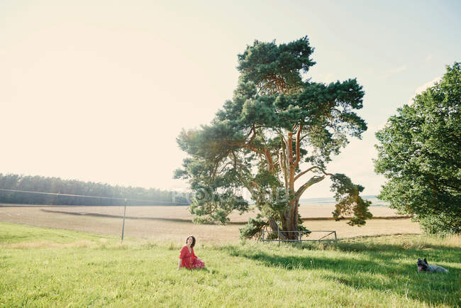 Pregnant woman sitting in field — Stock Photo