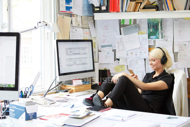 Female with feet up at desk — Stock Photo