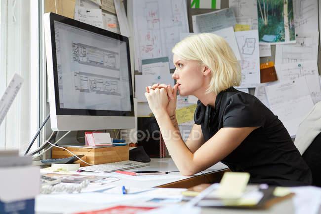 Designer donna che fissa dalla scrivania dell'ufficio — Foto stock