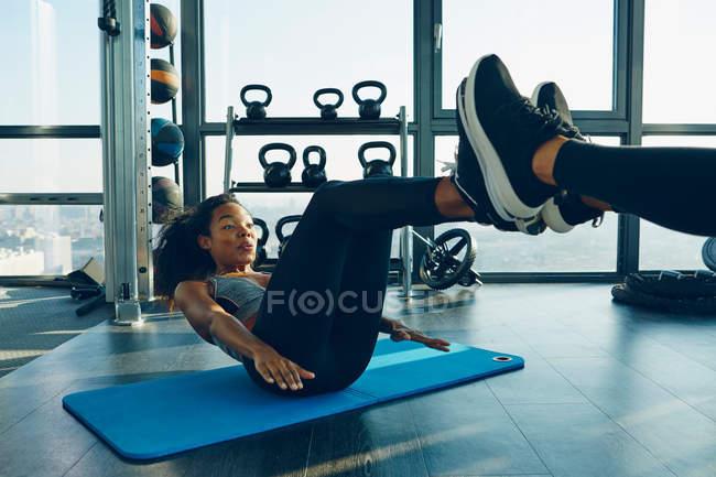 Dos mujeres jóvenes haciendo ejercicio en el gimnasio - foto de stock