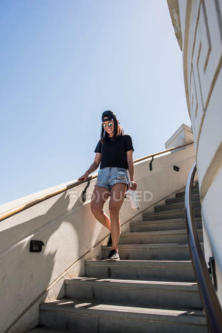 Young woman moving down stairway — Stock Photo