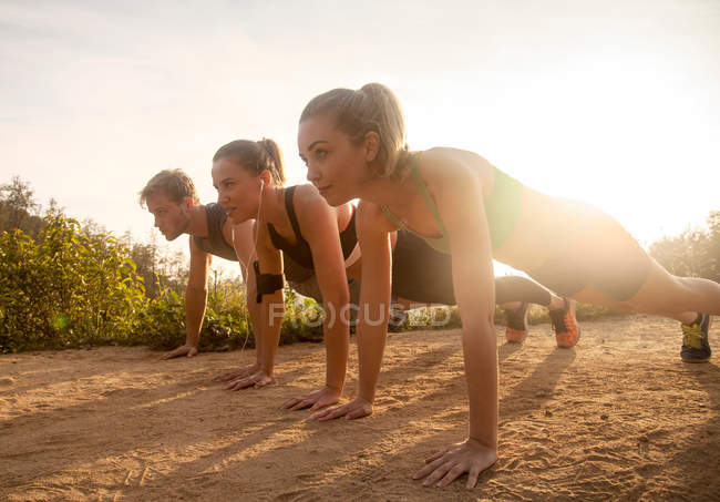 Three friends exercising outdoors, doing push-ups — Stock Photo