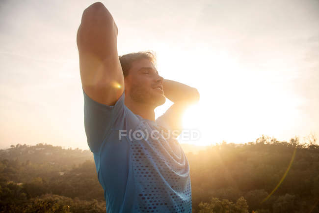 Young man outdoors, wearing sports clothing, hands behind head, smiling — Stock Photo