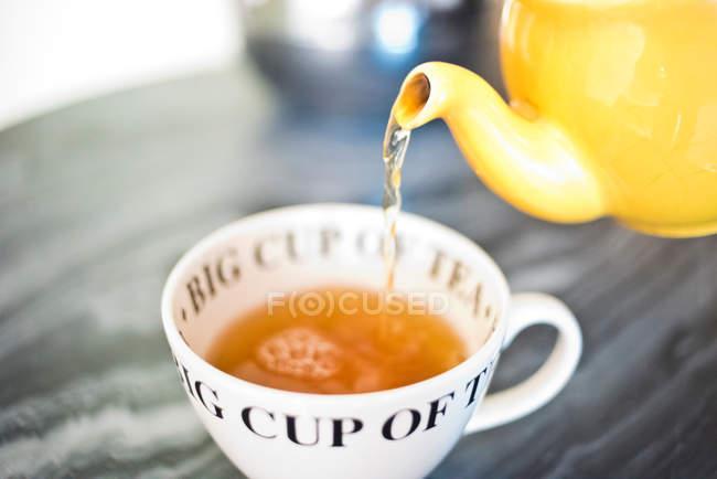 Tea pouring into teacup — Stock Photo