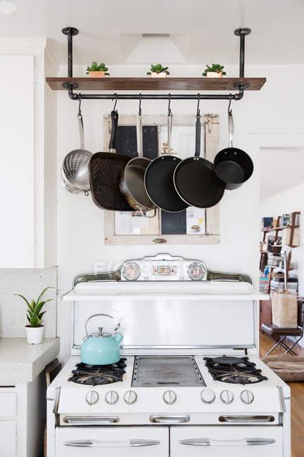 Каструлі висить над плитою кухні — стокове фото