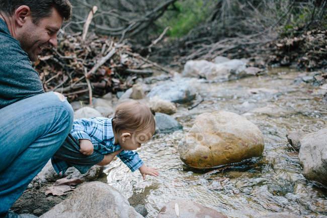 Pai e bebê menino investigando rio — Fotografia de Stock