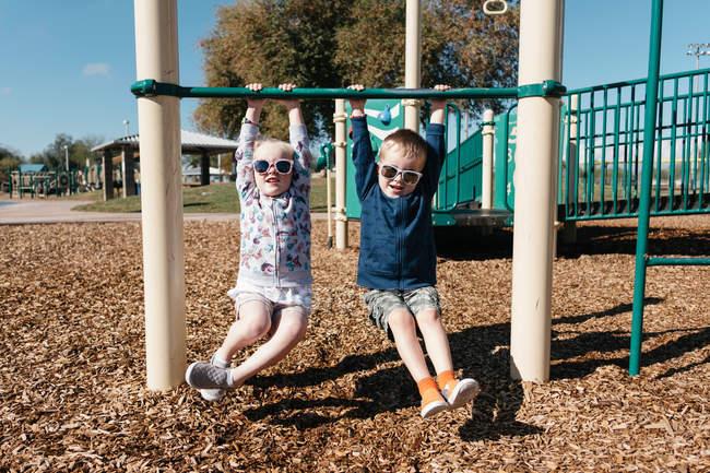 Menino e menina pendurados no quadro de escalada — Fotografia de Stock