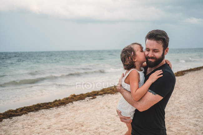 Preteen daughter kissing father at seaside — Stock Photo