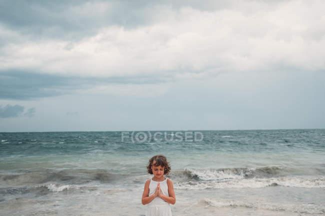 Jeune fille priant sur la plage — Photo de stock