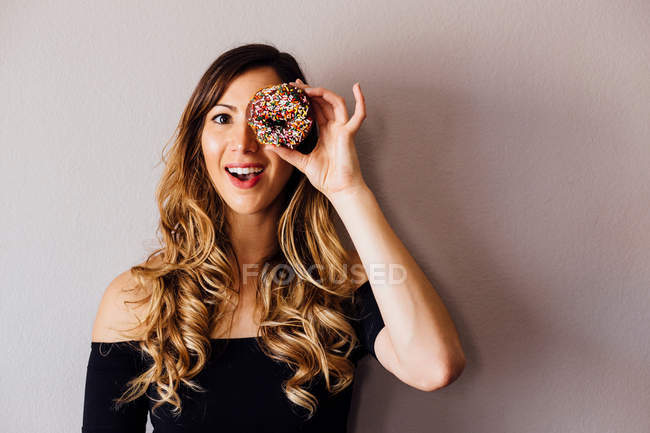 Young woman holding doughnut hole — Stock Photo