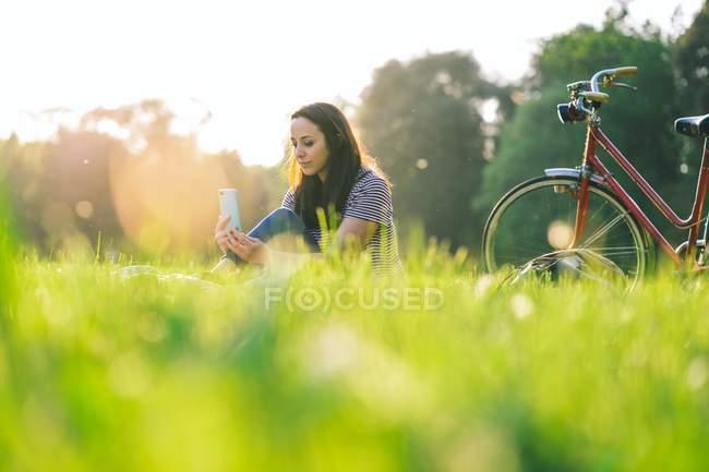 Frau benutzte Handy auf Gras — Stockfoto