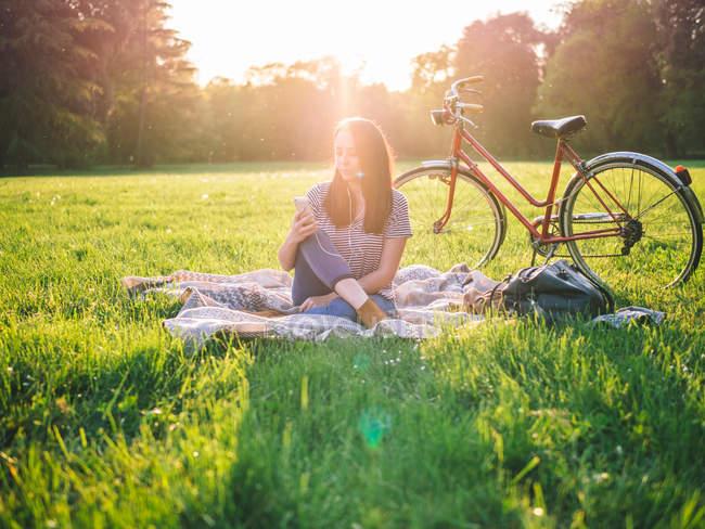 Frau benutzt Handy auf Gras — Stockfoto