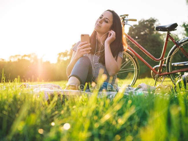 Woman using phone on grass — Stock Photo