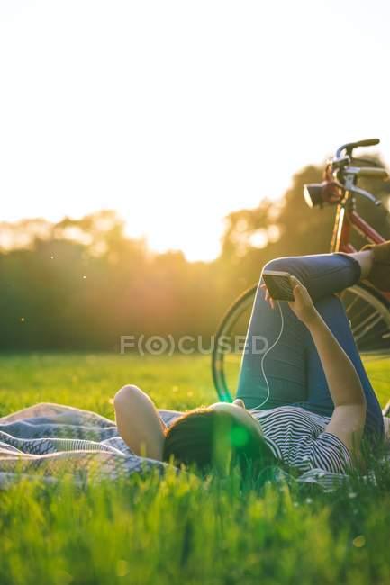 Женщина с телефоном на траве — стоковое фото