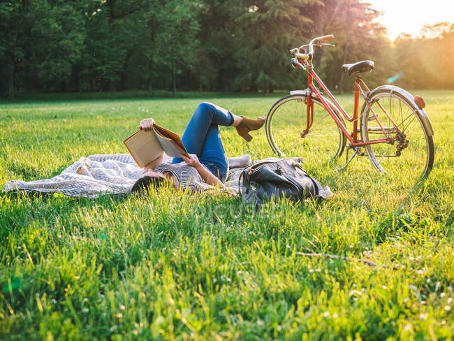 Woman reading book on grass — Stock Photo
