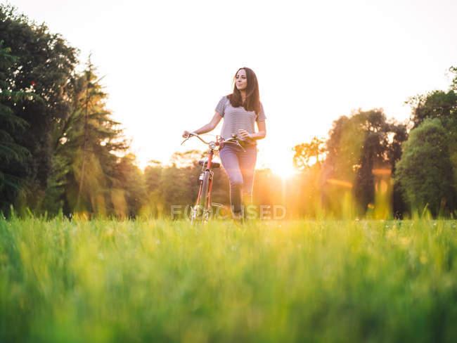 Frau läuft Fahrrad auf Gras — Stockfoto
