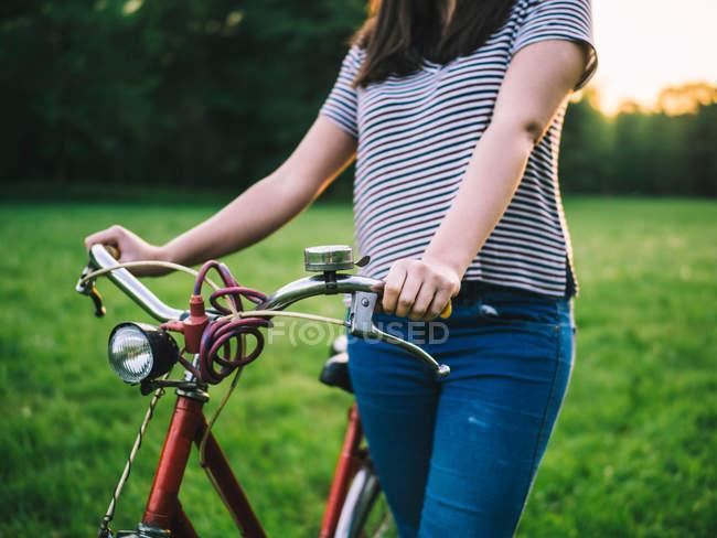 Woman walking bicycle on grass — Stock Photo