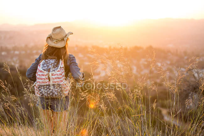 Woman hiking, wearing stars and stripes backpack, rear view — Stock Photo