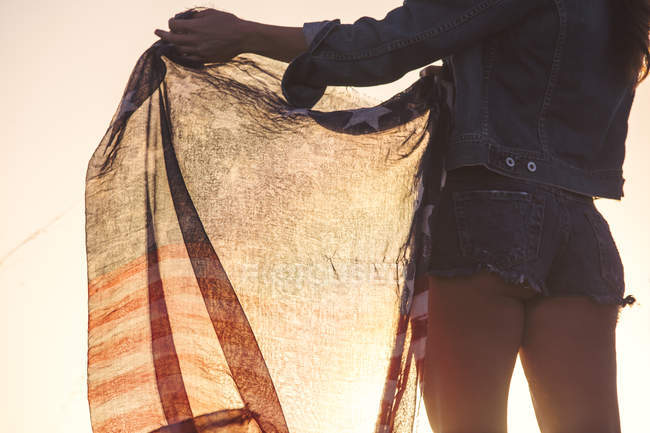 Woman wearing denim shorts, holding American flag, mid section, rear view — Stock Photo