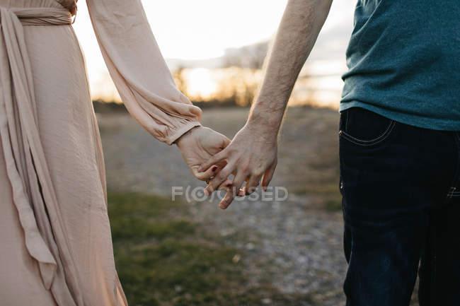 Пара держащихся за руки на улице, средняя секция, крупный план — стоковое фото