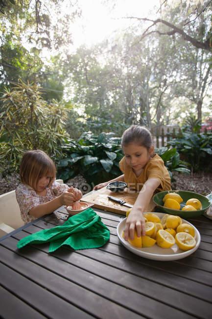 Two young sisters preparing lemons for lemonade at garden table — Stock Photo