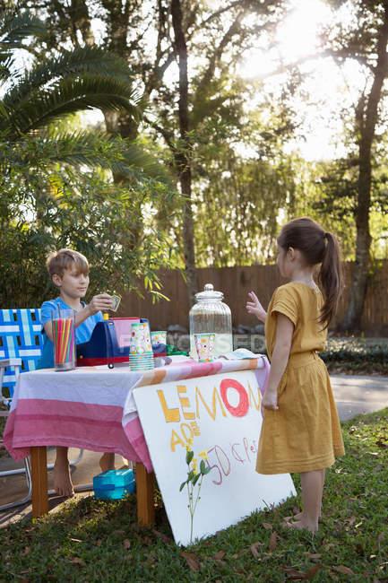 Mädchen kauft Limonade am Limonadenstand im Garten — Stockfoto
