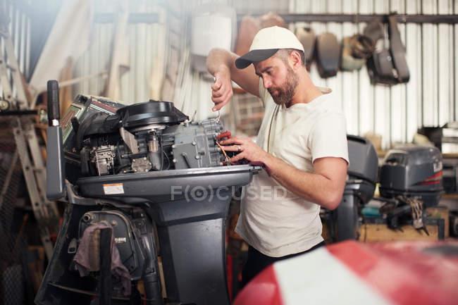 Людина ремонту підвісних двигуна в майстерні ремонт човен — стокове фото
