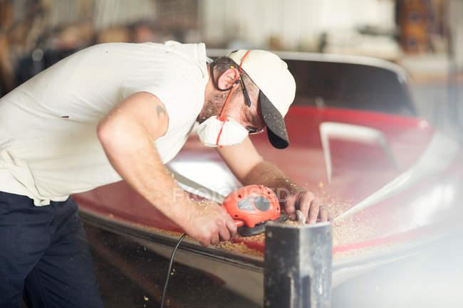 Homme travaillant avec la machine de polissage dans l'atelier de réparation de bateau — Photo de stock