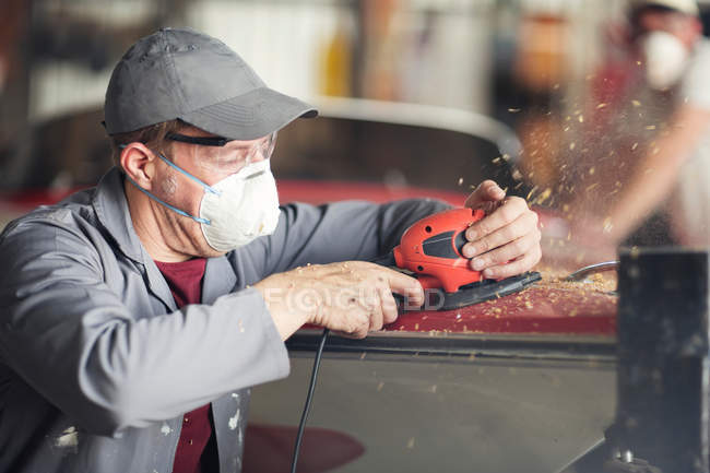Man sanding bodywork in boat repair workshop — Stock Photo