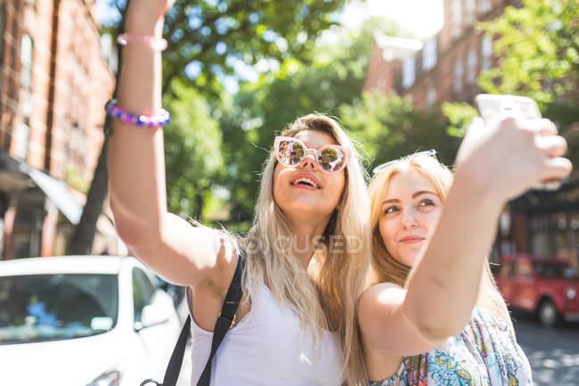 Zwei Mädchen, die die Selfie mit smartphones — Stockfoto