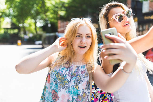 Two girls taking selfie with smartphones — Stock Photo