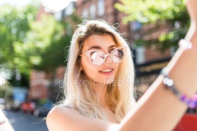 Teenage girl taking selfie with smartphone — Stock Photo
