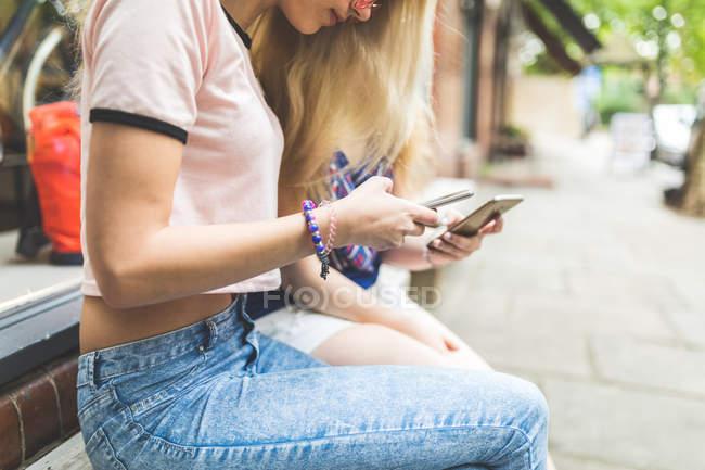 Filles, assis à la rue et à l'aide de smartphones — Photo de stock