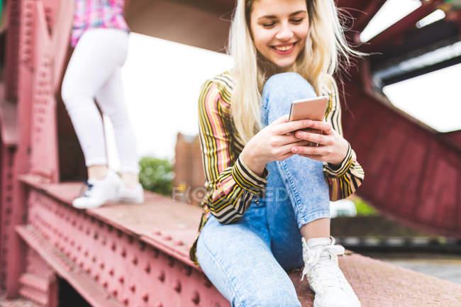 Filles sur pont avec smartphone — Photo de stock
