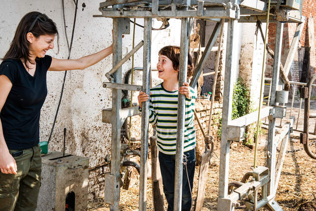 Female farmer and boy in animal stall — Stock Photo