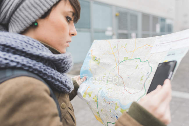 Female backpacker looking at map — Stock Photo