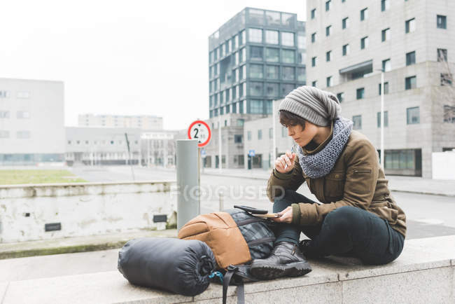 Female backpacker looking at notebook — Stock Photo