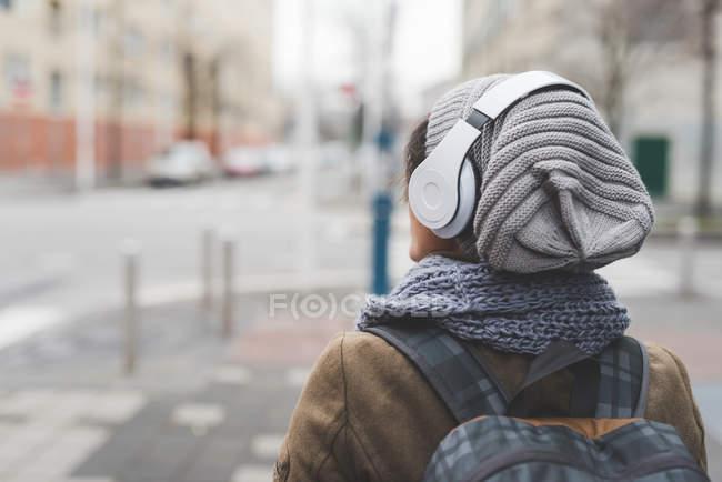 Zaino in spalla femminile ascolto cuffie — Foto stock