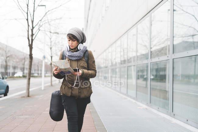 Mochilero femenino con smartphone - foto de stock