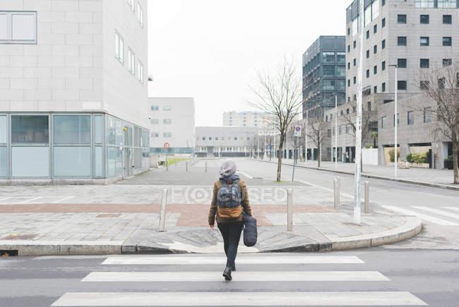 Female backpacker walking over pedestrian crossing — Stock Photo