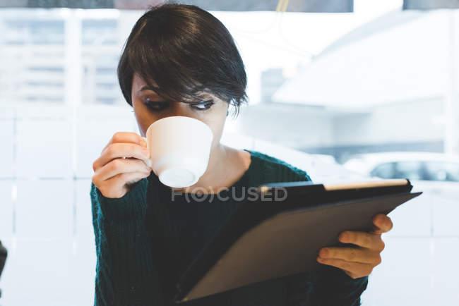 Frau schaut auf Tablet und trinkt — Stockfoto
