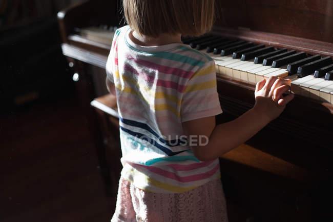 Дівчинка стоїть і грати на фортепіано — стокове фото