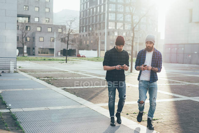 Hipsters walking in city while looking at smartphones — Stock Photo