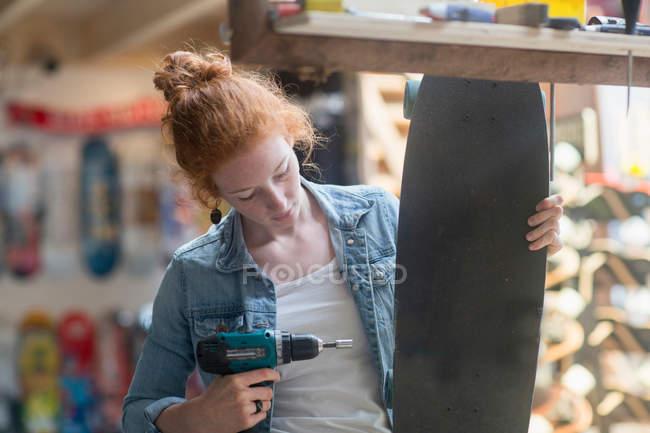 Женщина работает в магазине скейтбордов — стоковое фото