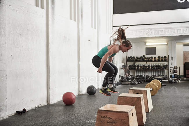 Woman jumping onto fitness box — Stock Photo