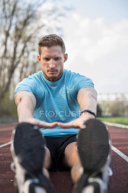 Man sitting on sports track — Stock Photo
