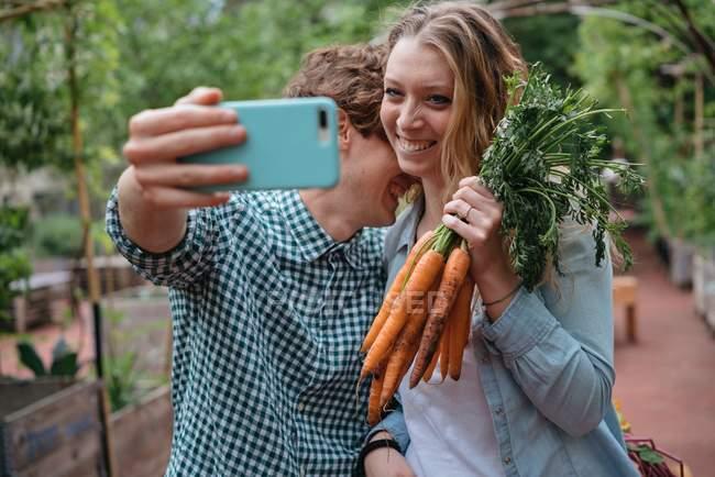 Pareja en jardín con zanahorias - foto de stock