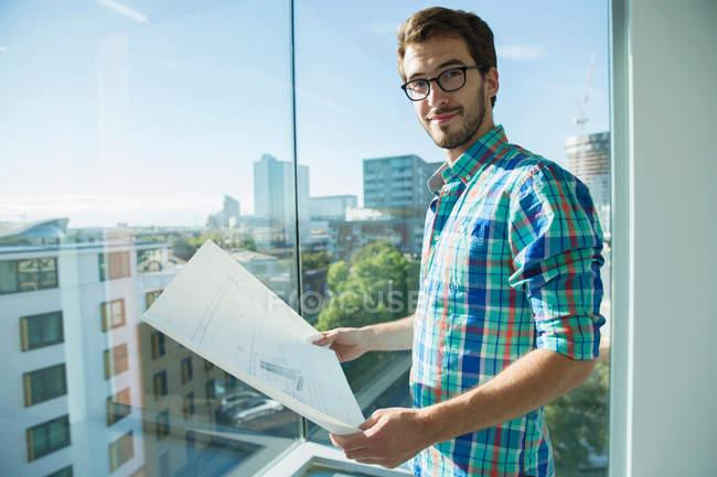 Mann steht neben Fenster — Stockfoto